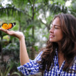 Butterfly sitting on the hand of a young woman i — Stock Photo #3205253