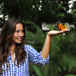 Stock Photo: Butterfly sitting on hand of young womi