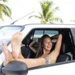 Car rental: woman relaxing in her car near the b — Stock Photo