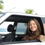 Car rental: happy woman in her car near the beac — Stock Photo