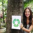 Stock Photo: Recycling: woman in the forest holding a recycle