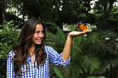 Butterfly sitting on the hand of a young woman i — Stock Photo