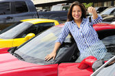 Woman showing key of new sports car — Stock Photo