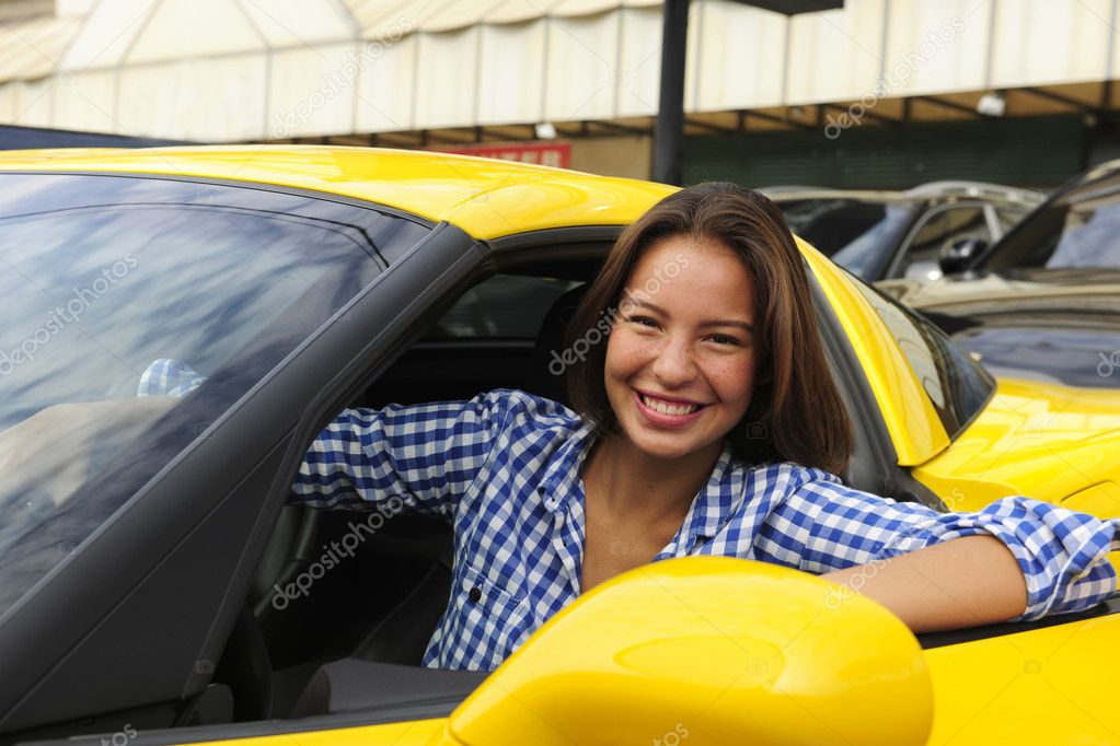 Happy woman sitting inside of her new yellow sports car — Stock Photo #3205363