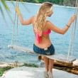 Blonde on rope swings - Stock Photo