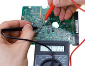 Printed circuit board and multimeter — Stock Photo