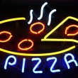 Neon Pizza Sign on Black - Stock Photo