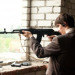 Young man shoots from window — Stock Photo