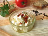 Cheese in herbs oil — Stock Photo