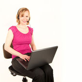 Young woman with laptop and headset — Stock Photo