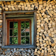Stock Photo: Stack of firewood with window