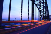 Light trails on the bridge at dusk — Stock Photo