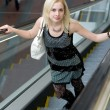 Beautiful young woman walking on escalat — Stock Photo