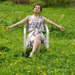Royalty-Free Stock Photo: Girl resting in a chair among dandelions