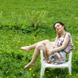 Girl resting in a chair among dandelions - Stock Photo
