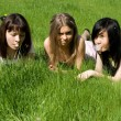 Three girls lying on grass — Stock Photo