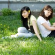 Two girls sitting on grass — ストック写真