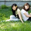 dwie dziewczyny, siedząc na trawie — Zdjęcie stockowe