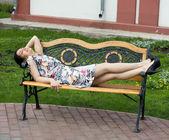 Girl lying on bench — Stock Photo