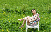 Girl resting in a chair among dandelions — Stock Photo