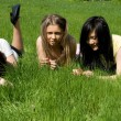 Stock Photo: Three girls lying on grass