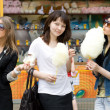 Three girls eating candy floss — Foto de Stock