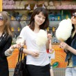 Three girls eating candy floss — Stockfoto