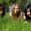 Three girls lying on grass — Stok fotoğraf