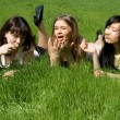 图库照片: Three girls lying on grass