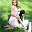 Three girls sitting on grass — Stok fotoğraf