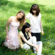 Three girls sitting on grass — ストック写真