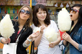 Three girls eating candy floss — Stock Photo