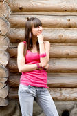 Girl standing near wooden wall — Stockfoto
