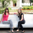 Two female friends sitting on bench - Stock Photo
