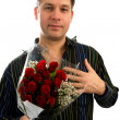 Young man in love is giving red roses — Stock Photo