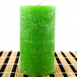 Green candle on reed mat — Stock Photo