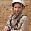 Stock Photo: Young girl posing before climbing wall