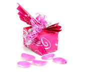 Beautiful wrapped gift with rose leaves — Stock Photo