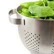 Colander filled with fresh spinach — Stock Photo