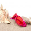 Pink sunglasses on the beach — Stock Photo