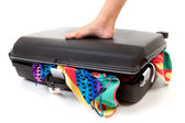 Foot on stuffed suitcase — Stock Photo