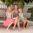Mother and daughters sitting on a wooden bench — Stock Photo
