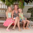 Mother and daughters sitting on a wooden bench — Stock Photo #3647930