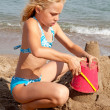 Girl is making sandcastle on the beach — Stockfoto