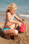Girl is making sandcastle on the beach — Stock Photo