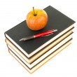 Stack of books with apple and pen — Stock Photo