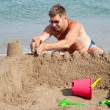 Stock Photo: Man is making sandcastle on the beach