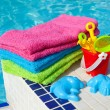 Towels and plastic toys near the swim pool - Stock Photo