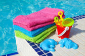 Towels and plastic toys near the swim pool — Stock Photo