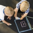 Two boys drawing house on asphalt — Stock Photo #3188317